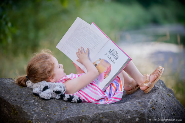 Portrait of a girl reading fairy tales on a rock by a river.