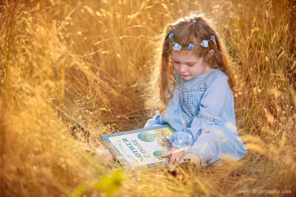Girl in blue dress reading mother goose book in field.