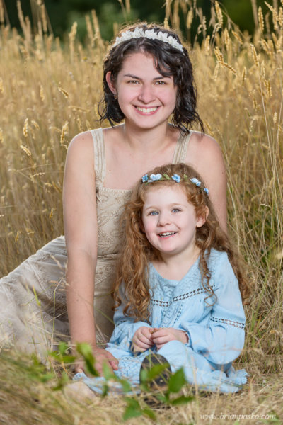 Portrait of two sisters with flower headbands sitting in a field with dresses.