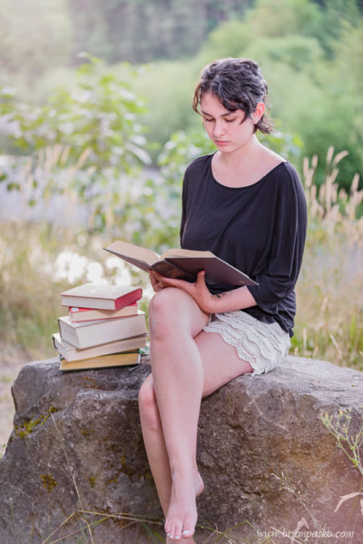 High school senior portrait of girl reading by a river.