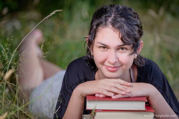 High School senior portrait of a girl laying in grass with school books.