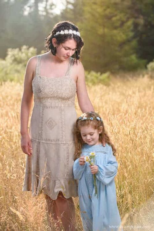 Portrait of two sisters in a field with daisies and vintage dresses.