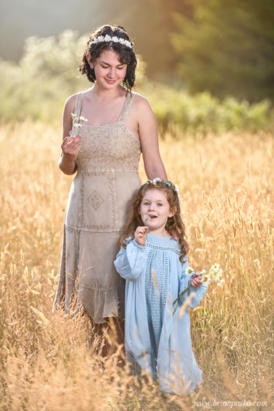 Portrait of two sisters blowing flowers in a field with vintage dresses.