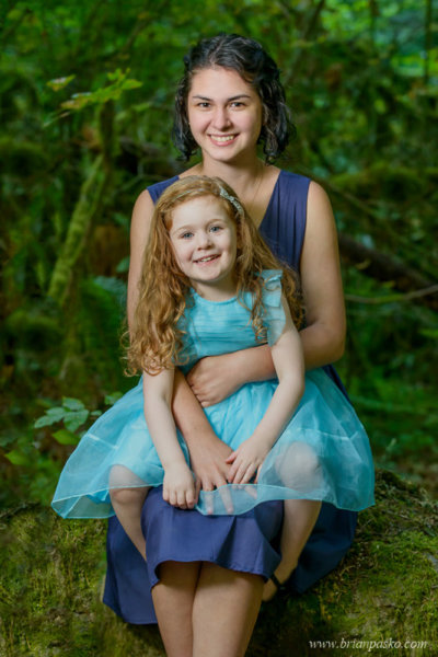 Portrait of two sisters in blue dresses in old growth forest.