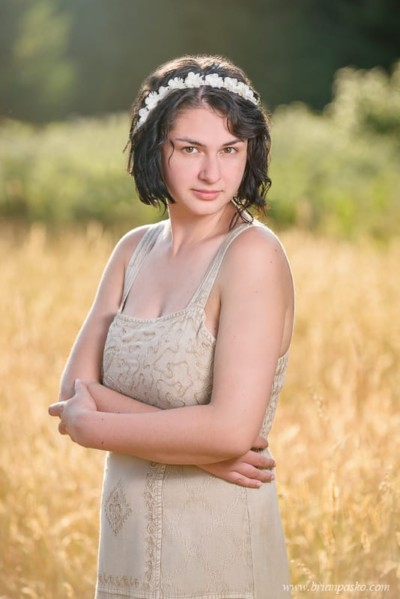 High school senior girl in golden field with vintage dress and white flower headband.
