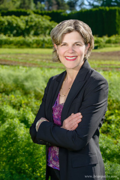 On location headshot portrait of a woman in business suit standing in a farm field.