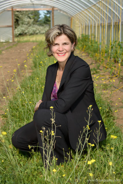 On location headshot portrait of a woman in business suit visiting a client greenhouse.