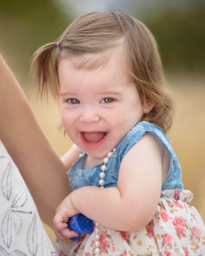 Thirteen month old baby girl in dress and pearls in her mom's arms at Powell Butte Nature Park in Portland.