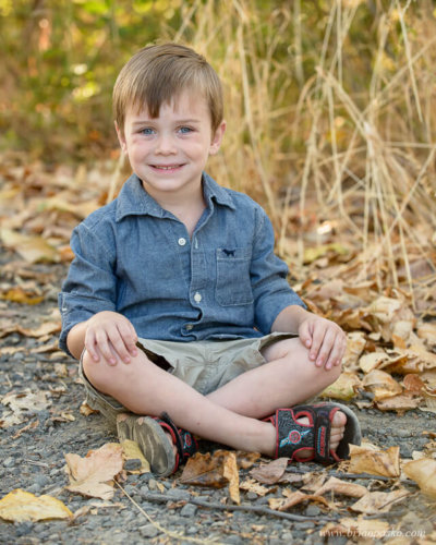 Four year old boy sitting in fall leaves at Powell Butte Nature Park in Portland, Oregon.