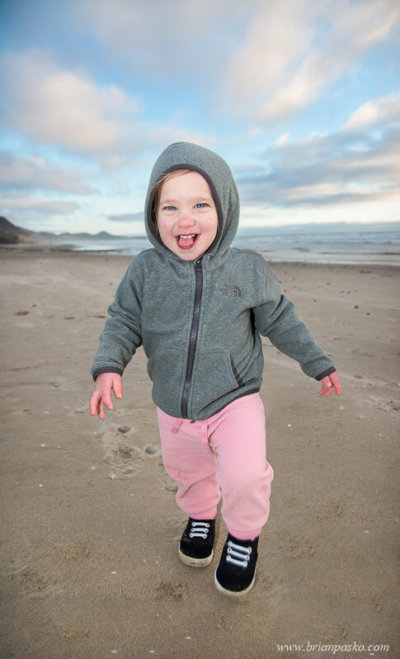 Two year old girl running on a chilly day with dramatic skies on Beverly Beach in Oregon.