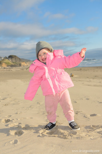 Two year old in a pink coat making footprints in the sand on a chilly day on Beverly Beach in Oregon.