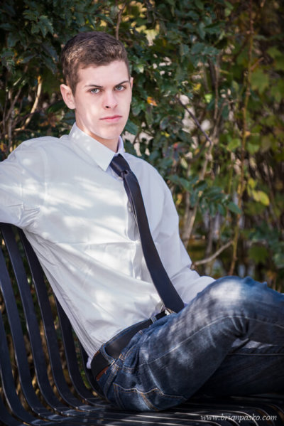 High school senior portrait of a senior boy in shirt, tie and jeans looking cool with picture on park bench.