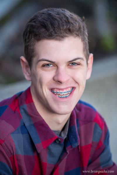 Senior picture of high school senior boy with headshot portrait in flannel shirt.