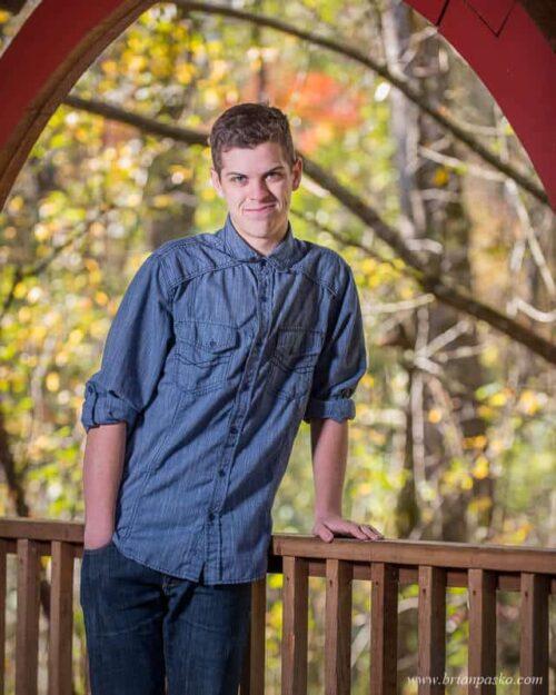 Senior picture of high school senior boy with portrait showing architecture of a wooden bridge at Fairview Community Park