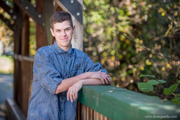 Casual portrait of a high school senior boy on bridge at Fairview Community Park.