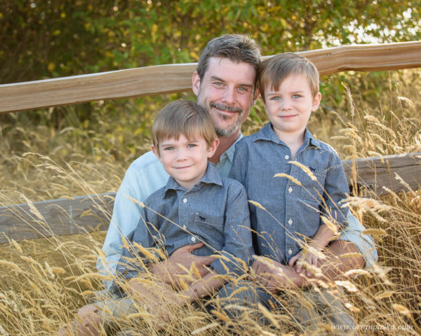 Portrait of Dad and his boys near fence at Powell Butte Nature Park in Portland, Oregon.