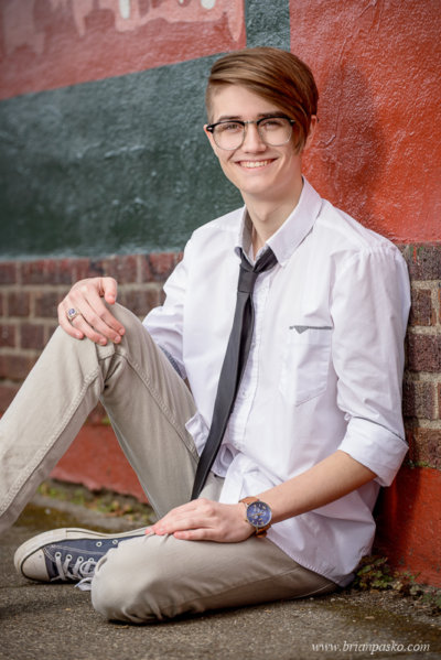 Southridge High School Senior boy in shirt and tie with senior portraits against brick wall on Alberta Street in Portland, Oregon.