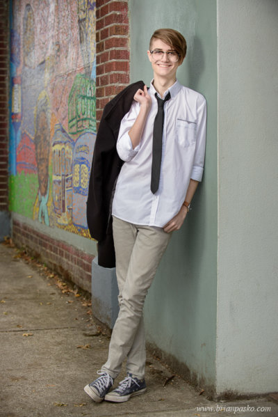Portrait of Southridge High School senior boy in shirt and tie with coat leaning against wall on Alberta Street in Portland, Oregon.