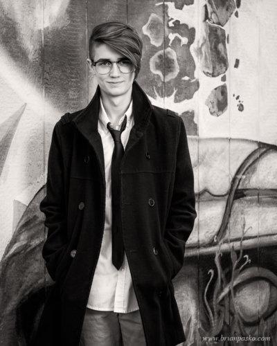 Black and white portrait of Southridge High School senior boy against mural on Alberta Street in Portland, Oregon.