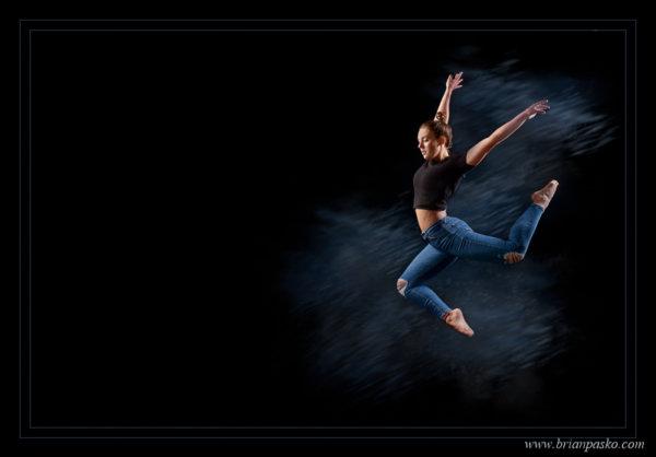 Portrait of high school senior dancer leaping through air.