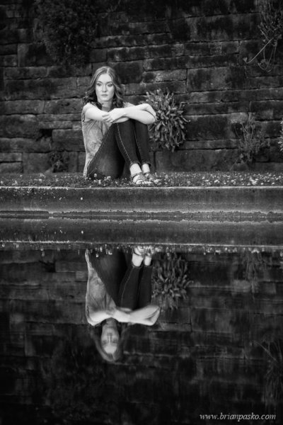Artistic black and white portrait of high school senior girl in reflection pool.