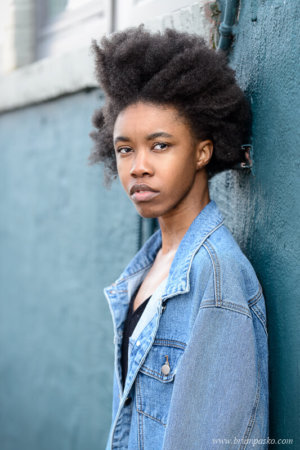 Urban portrait og high school girl against blue wall.