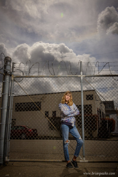 Grungy fashion portrait of high school girl against urban fence with creative lighting.