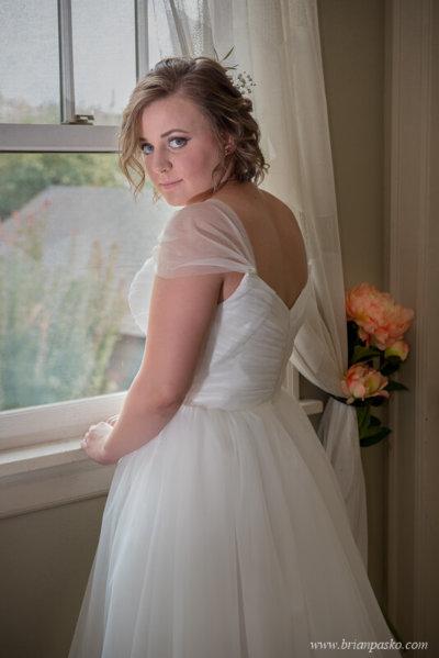 Bride standing in front of window before her wedding near Laurelhurst Park in Portland, Oregon.