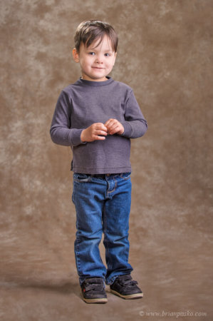 Portrait of boy in blue jeans and sweater taken in studio against a brown background with hair light.