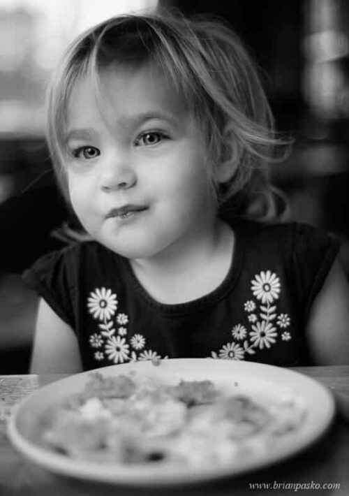 Black and white portrait of a toddler eating pancakes and eggs at Marias Cafe in Minneapolis, Minnesota.