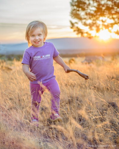 Portrait of a toddler with a stick playing at sunset in Eastern Oregon.