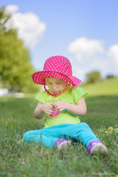 Portrait of a toddler in a colorful outfit sitting in the grass at a park in Minneapolis, Minnesota.