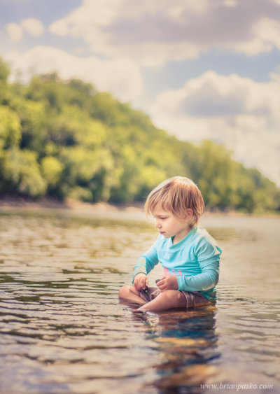 Portrait of a toddler sitting in the Mississippi River in Minneapolis Minnesota.