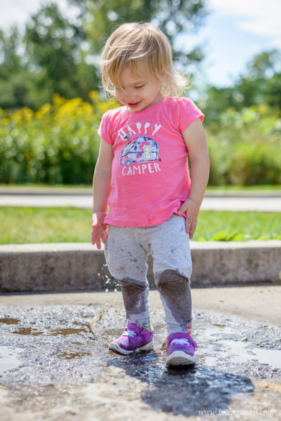 Portrait of a toddler splashing in a puddle at Powderhorn Park in Minneapolis, Minnesota.